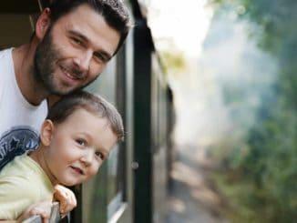 Vater und Sohn schauen aus dem Fenster eines fahrenden Zuges
