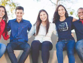 Fünf junge Menschen sitzen lachend auf einer Mauer