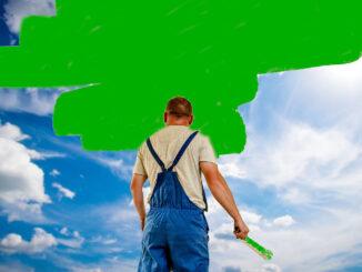 Ein Mann streicht eine Wand vor einem blauen Himmel grün an
