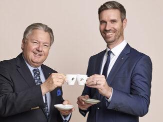 Zwei Männer stoßen mit Kaffeetassen an