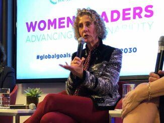 Eine Frau mit Mikrophon auf einem Podium