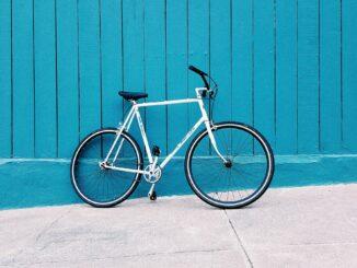 Ein weißes Fahrrad vor einer blauen Wand