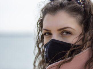 Eine junge Frau mit Gesichtsmaske vor dem Meer