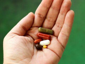 Eine offene Hand, in der verschiedene Medikamente liegen