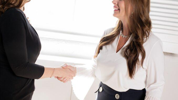 Zwei Frauen geben sich die Hand