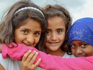 Drei kleine Mädchen, die sich umarmen