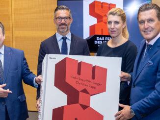 Vier Personen mit einem riesigen Buchcover